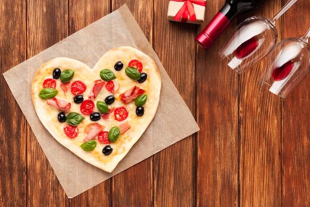 Pizza de configuração plana em forma de coração com vinho Foto gratuita