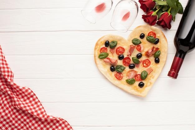 Pizza de configuração plana em forma de coração no fundo branco Foto gratuita