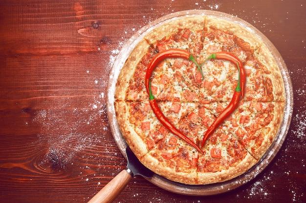 Pizza de dia dos namorados com pimentos em cima de uma pizza Foto Premium