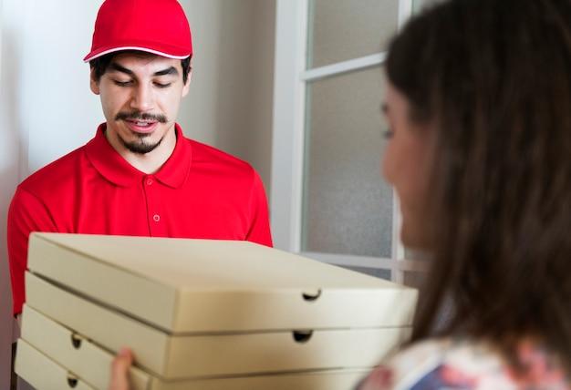 Pizza de entrega do homem ao cliente Foto gratuita