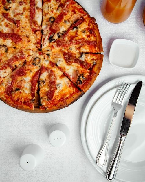 Pizza de frango com molho de azeitona, queijo e tomate Foto gratuita
