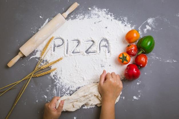 Pizza de palavra escrita na farinha com ingredientes Foto gratuita