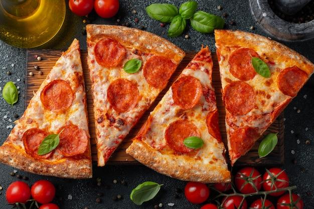 Pizza de pepperoni saborosa e ingredientes de cozinha Foto Premium
