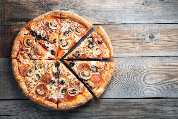 Pizza de pepperoni saboroso com cogumelos e azeitonas. Foto Premium