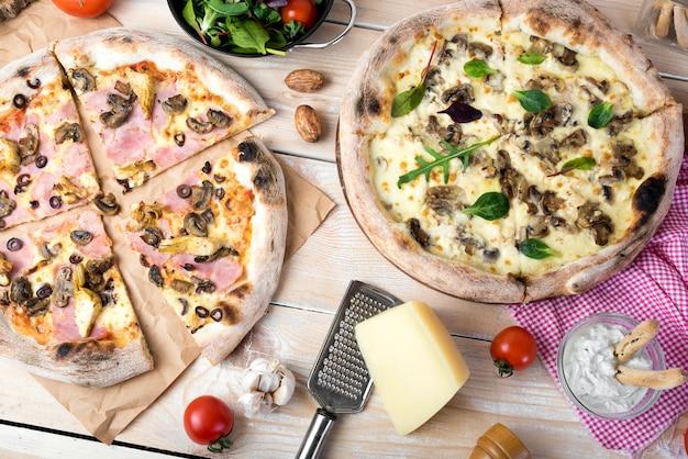 Pizza de queijo; salada com queijo; mergulho e legumes sobre a superfície de madeira Foto gratuita