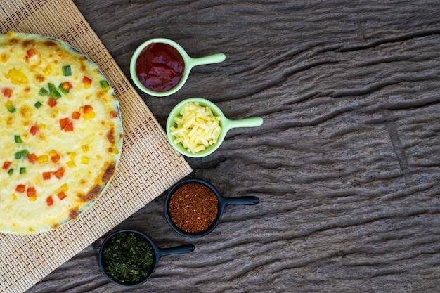 Pizza de vegetais caseira com tomate cereja e outros ingredientes em um fundo de madeira Foto Premium