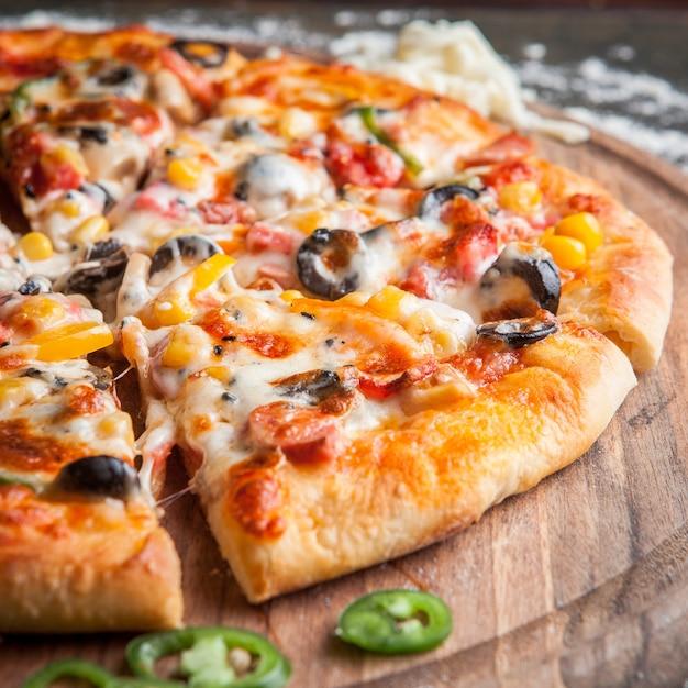 Pizza de vista lateral com pimenta picada em panelas de bordo Foto gratuita