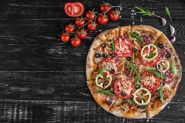 Pizza dos vegetais, dos cogumelos e dos tomates em um fundo de madeira preto. pode ser usado como pano de fundo Foto Premium