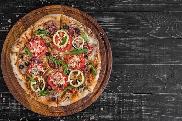Pizza dos vegetais, dos cogumelos e dos tomates em um fundo de madeira preto. Foto Premium