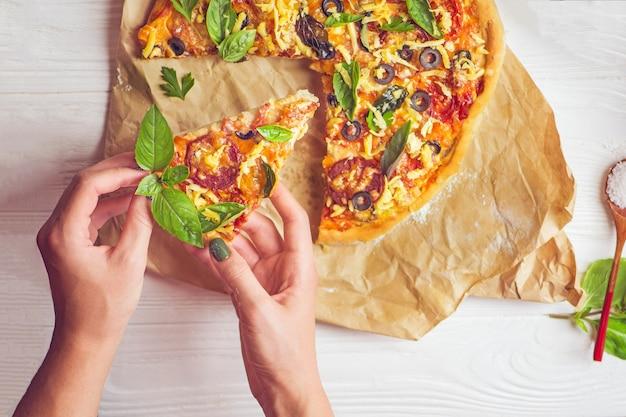 Pizza e mão close-up sobre fundo branco Foto Premium