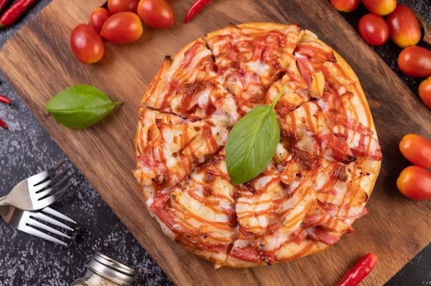 Pizza em uma bandeja de madeira com tomate pimenta e manjericão. Foto gratuita