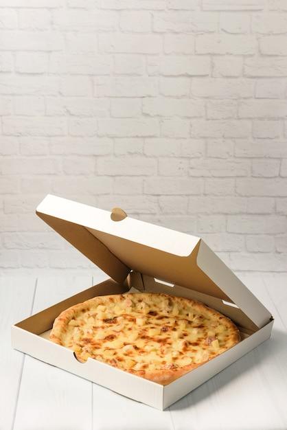 Pizza havaiana em uma caixa de papelão em um fundo de parede de tijolo branco com espaço de cópia. Foto Premium