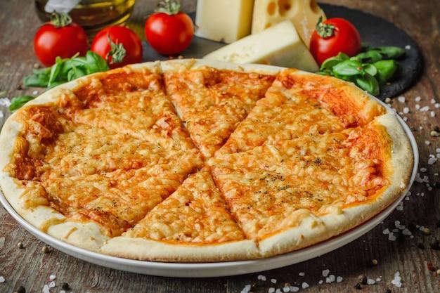Pizza italiana e ingredientes em uma mesa de madeira Foto Premium