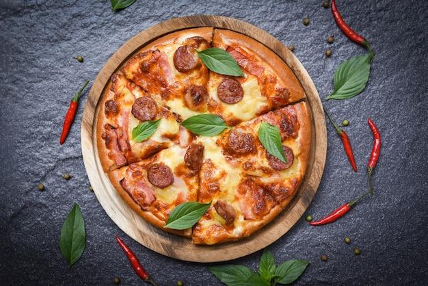 Pizza na bandeja de madeira e pimentão manjericão folha vista superior Foto Premium