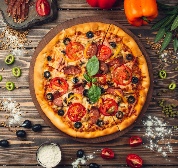 Pizza pizza cheia de tomates, salame e azeitonas Foto gratuita