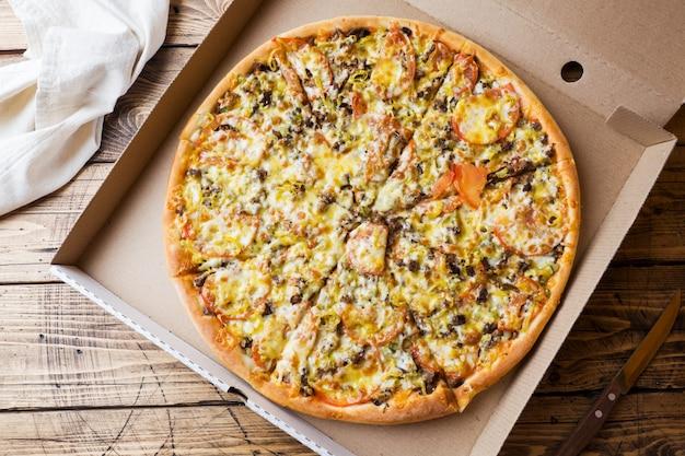 Pizza recentemente cozida em uma caixa de cartão em uma tabela de madeira. Foto Premium