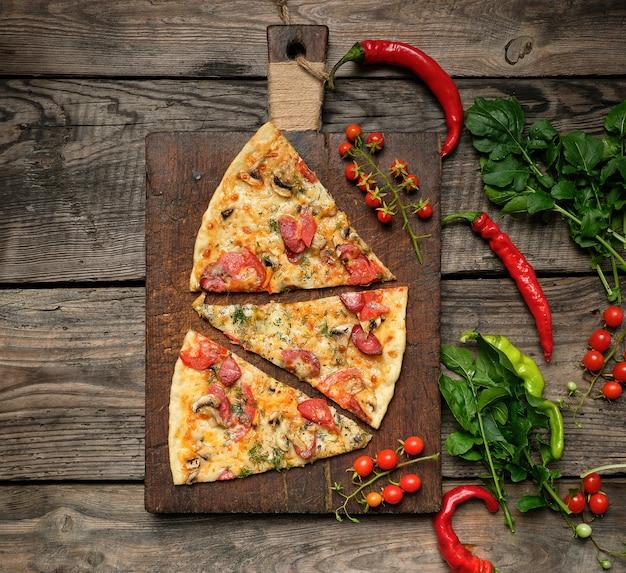 Pizza redonda assada com lingüiça defumada, cogumelos, tomate, queijo Foto Premium