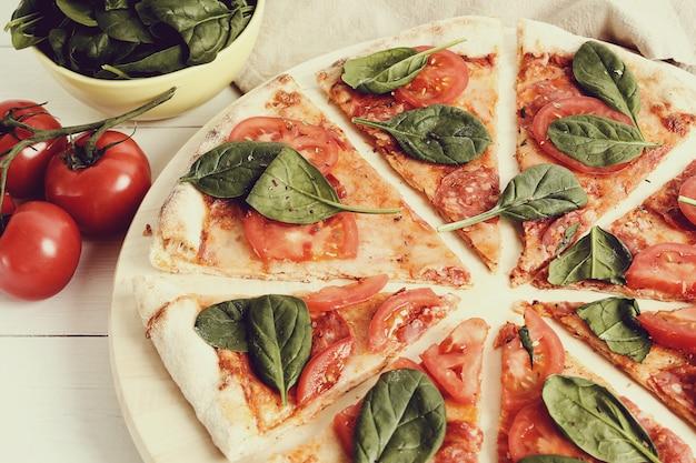 Pizza tradicional com fatias de tomate e folhas de manjericão Foto gratuita