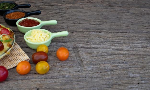 Pizza vegetariana caseira com tomate cereja e outros ingredientes em um fundo de madeira Foto Premium