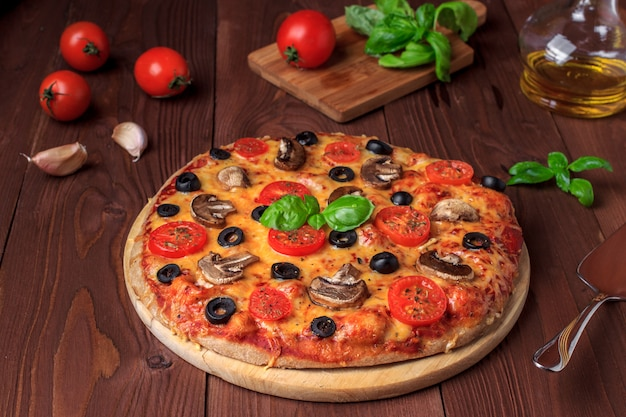 Pizza vegetariana com cogumelos, tomate cereja, azeitonas pretas e manjericão Foto Premium