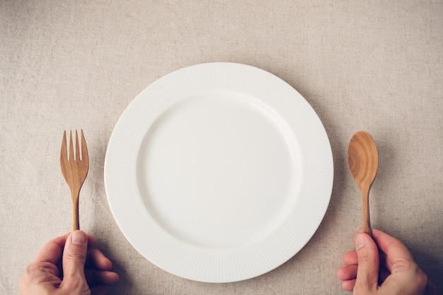 Placa branca com colher e garfo, conceito de jejum intermitente, dieta de perda de peso Foto Premium