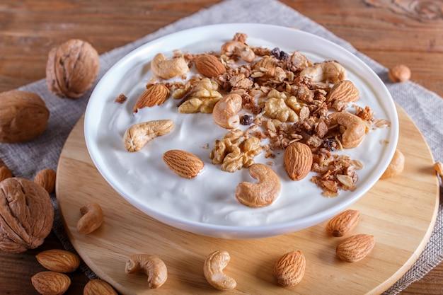 Placa branca com iogurte grego, granola, amêndoa, caju, nozes em madeira marrom. Foto Premium