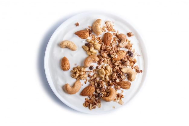 Placa branca com o granola grego do iogurte, amêndoa, caju, nozes isoladas na superfície branca. Foto Premium