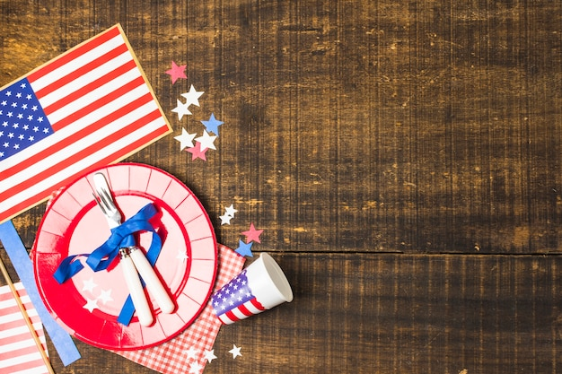 Placa de bandeira de eua e talheres amarrado com fita azul com bandeira; estrela e copo descartável na mesa de madeira Foto gratuita