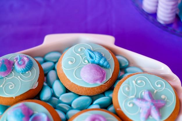 Placa de casca branca cheia de bombons de chocolate com cobertura azul, biscoitos com conchas, estrelas na mesa Foto Premium