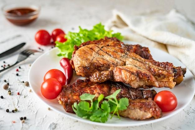 Placa de cerâmica branca com carne de porco grelhada, folhas de alface, tomate e pimenta vermelha e molho nas tigelas Foto Premium