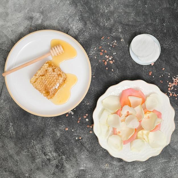 Placa de cerâmica branca com favo de mel; dipper e pétalas de rosa com almofadas de algodão redondas brancas em pano de fundo preto concreto Foto gratuita