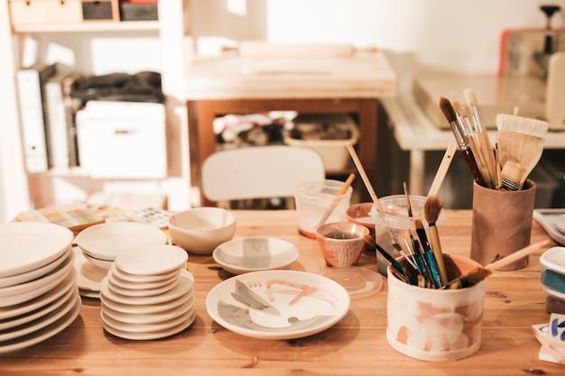 Placa de cerâmica e tigela com pincéis e ferramentas na mesa de madeira na oficina Foto gratuita