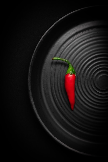 Placa de cerâmica preta redonda com padrão de círculos com pimenta vermelha fresca Foto Premium