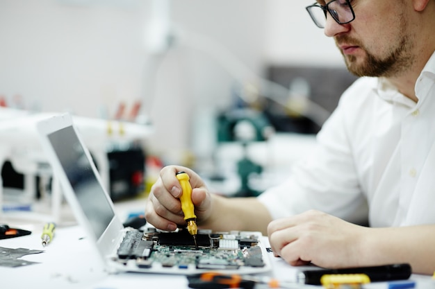 Placa de circuito de montagem do homem no laptop Foto gratuita