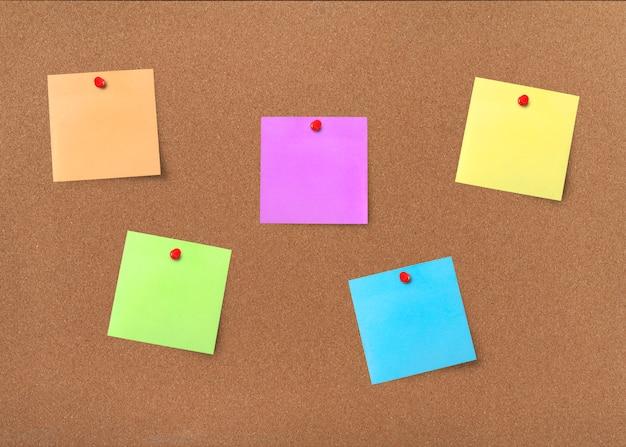Placa de cortiça com notas em branco coloridas com traçado de recorte Foto Premium