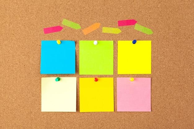 Placa de cortiça com várias notas em branco coloridas com pinos Foto Premium
