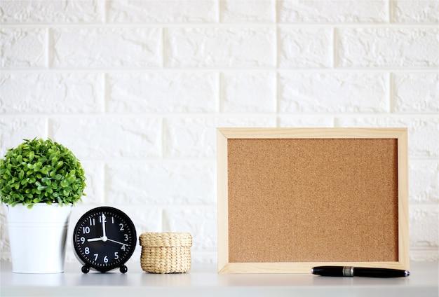 Placa de cortiça em branco simulado acima com relógio, plantas verdes na parede de tijolo branco Foto Premium
