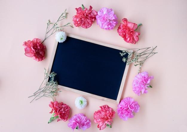 Placa de giz preto com flor cravo fresca no fundo creme suave com espaço de cópia Foto Premium