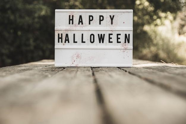 Placa de halloween colocada na mesa de madeira Foto gratuita