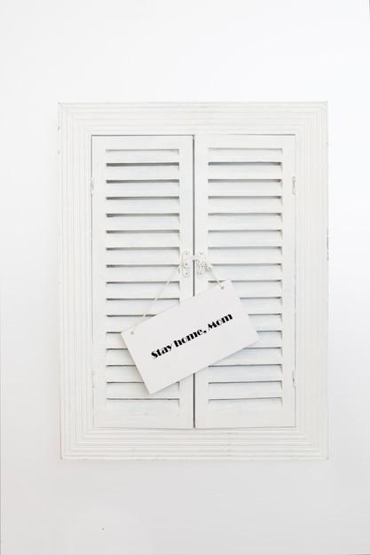 Placa de identificação com palavras fique em casa, mãe na janela de venezianas de madeira. conceito de quarentena em casa como medida preventiva contra o surto de vírus corona covid 19. Foto Premium