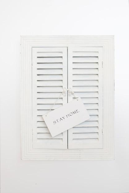 Placa de identificação com palavras fique em casa na janela de venezianas de madeira. conceito de quarentena em casa como medida preventiva contra o surto de vírus corona covid 19. Foto Premium