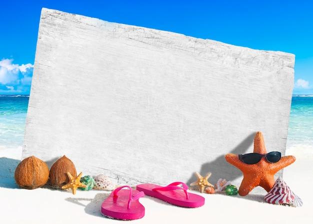 Placa de madeira branca com outros objetos pela praia Foto gratuita