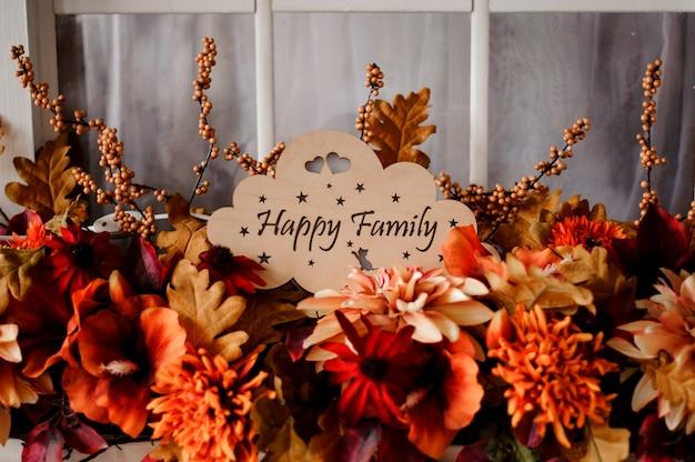 Placa de madeira com a família feliz inscrição entre flores Foto Premium