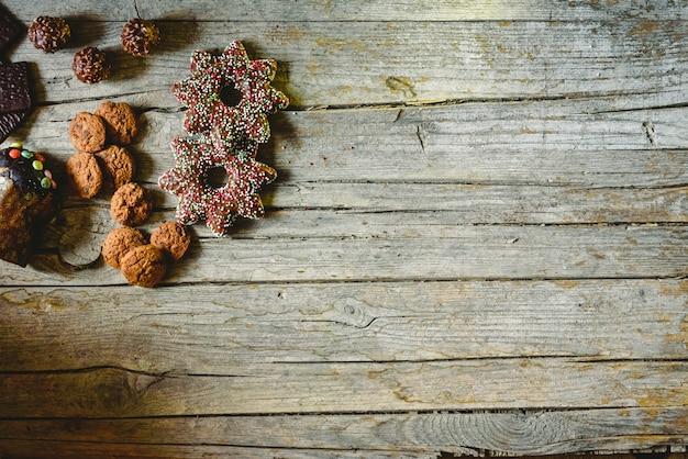 Placa de madeira envelhecida retrô com biscoitos de chocolate e doces em um canto com espaço para texto Foto Premium