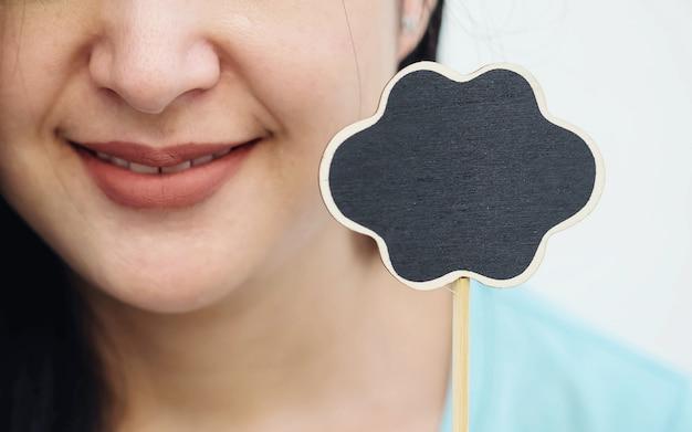 Placa de madeira preta closeup em forma de caixa de texto com rosto sorriso borrado de fundo de mulher Foto Premium