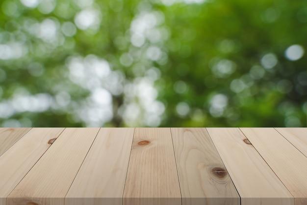 Placa de madeira sobre fundo verde turva natureza, perspectiva mesa de madeira vazia sobre desfocagem backgroun Foto Premium