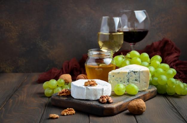 Placa de queijo com uvas, mel e porcas no fundo escuro. Foto Premium