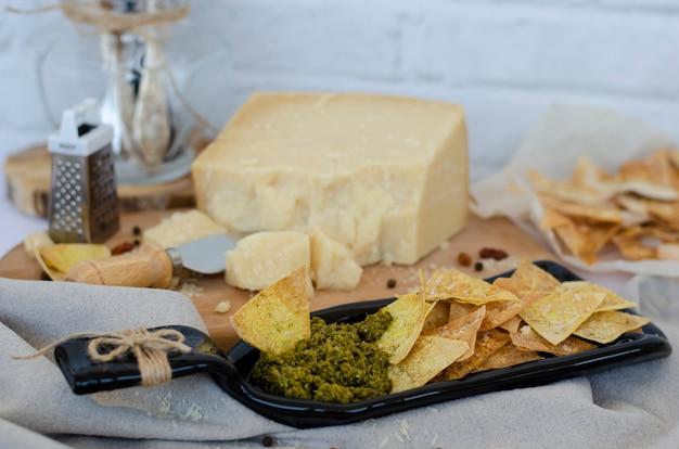 Placa de servir incomum feita de garrafa com batatas fritas caseiras e molho pesto italiano e queijo parmesão Foto Premium