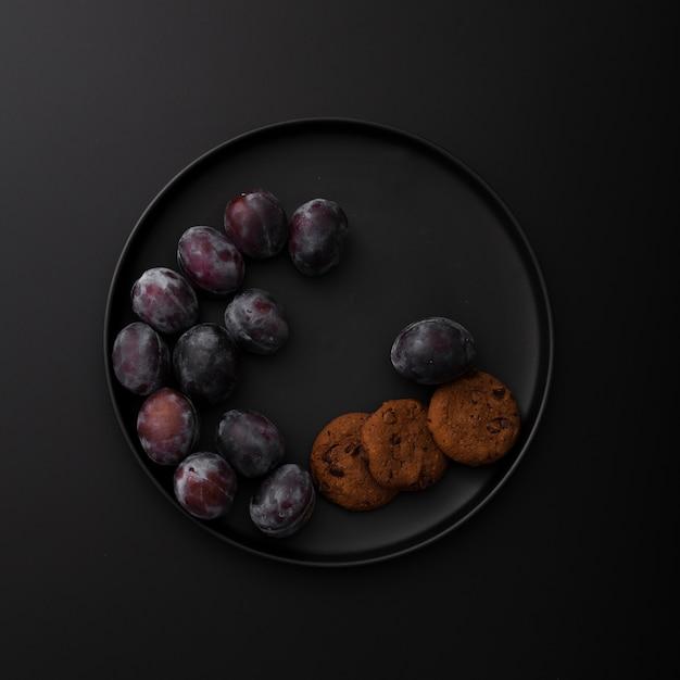 Placa escura com biscoitos e ameixas em um fundo escuro Foto gratuita