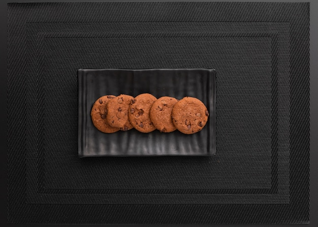 Placa escura com biscoitos em um pano escuro Foto gratuita